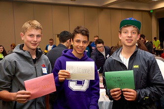 Teens hold welcome cards for refugees.