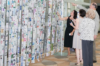 Guests view the Living Legacy Tapestry at the 20th anniversary event.